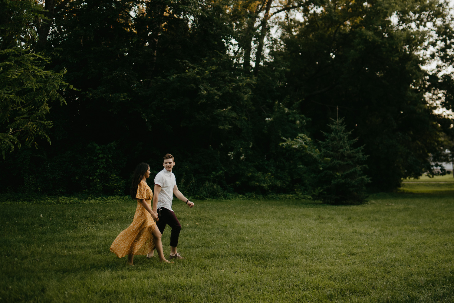 Man and woman walking through field from far away