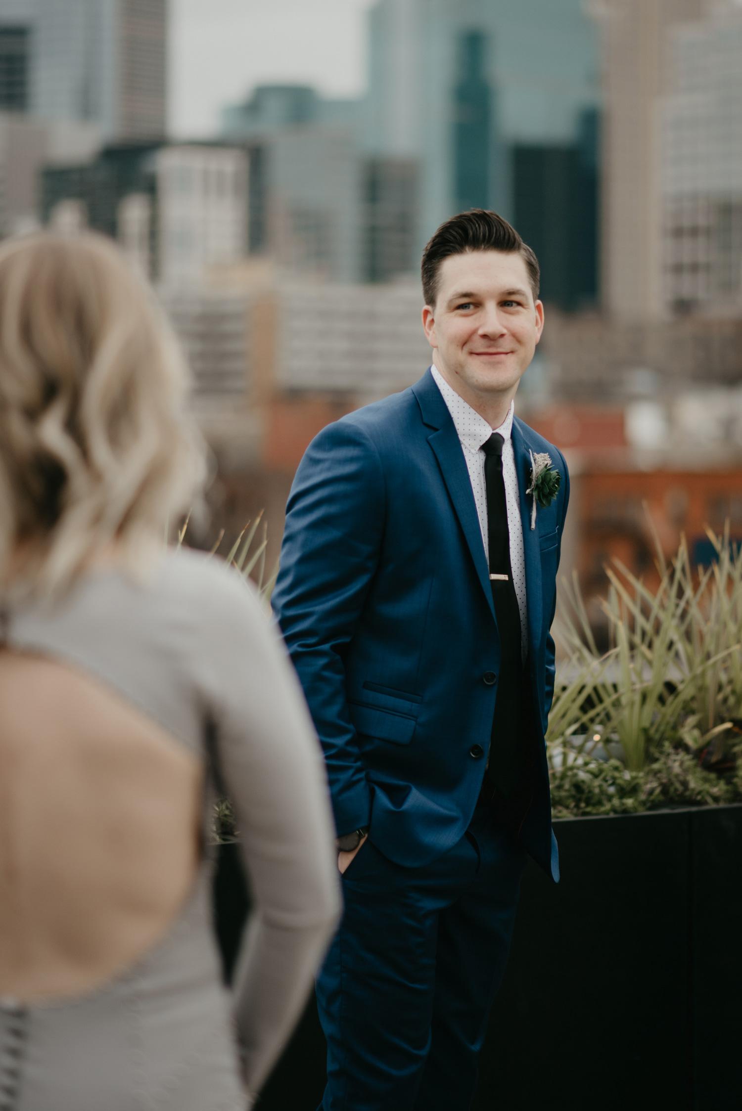 Groom seeing bride first look blue suit rooftop