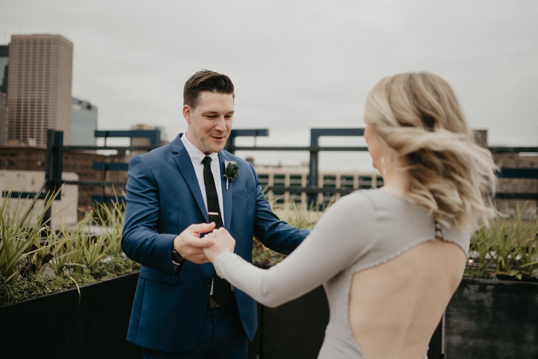 Groom seeing bride first look blue suit downtown Minneapolis rooftop