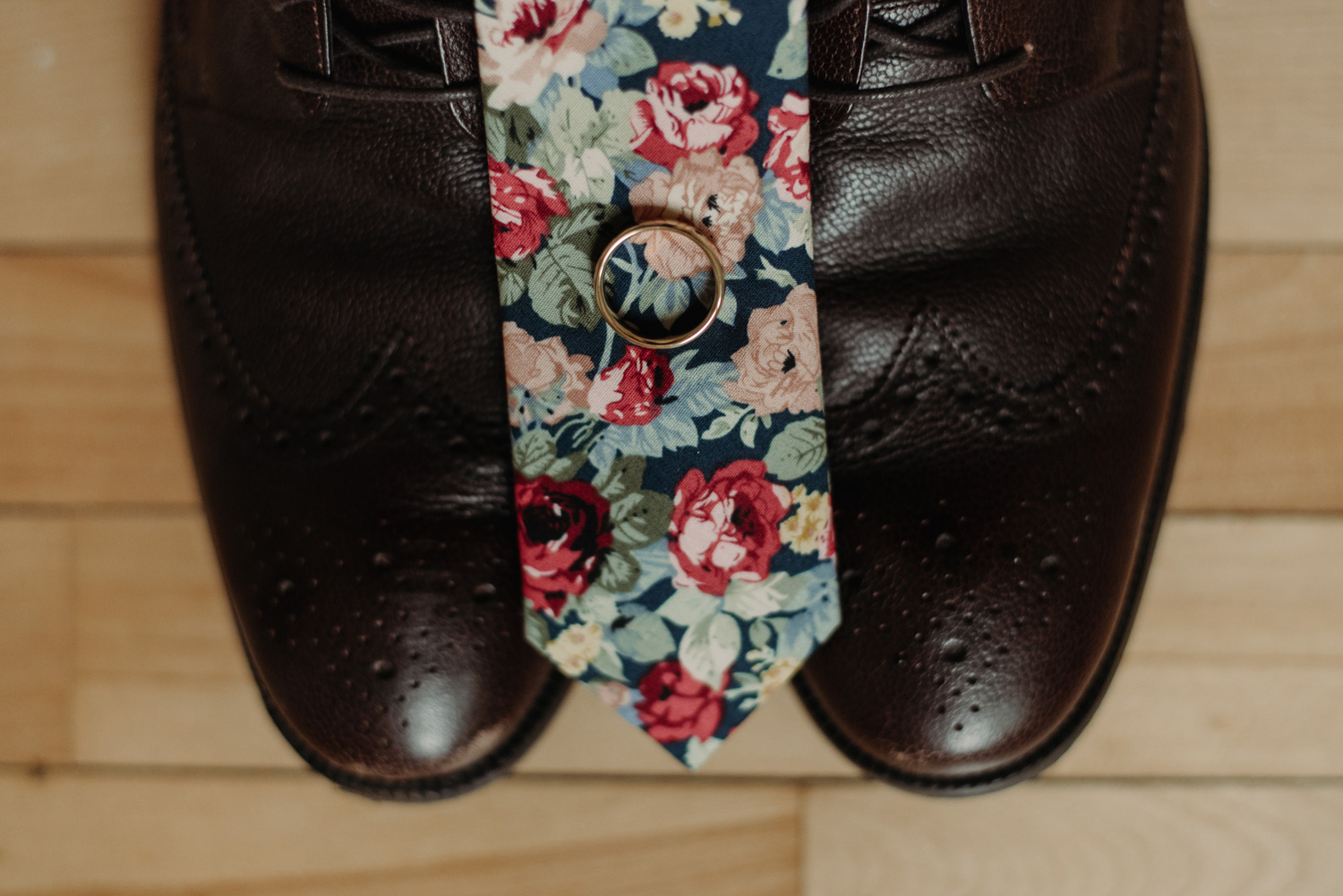 brown groom's shoes with floral tie and wedding ring