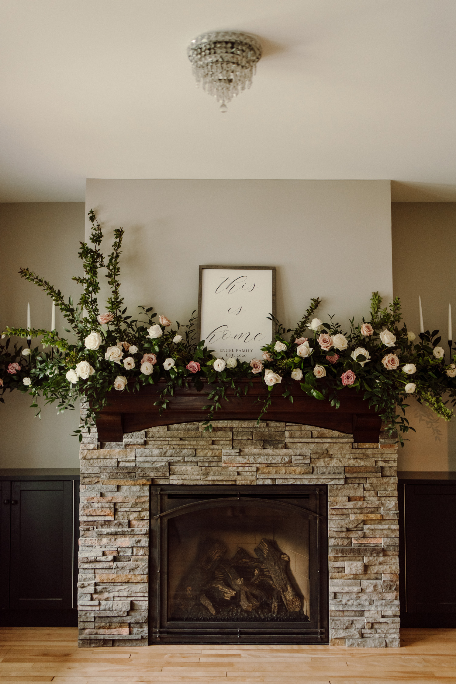 fireplace mantle decorated with wedding floral roses