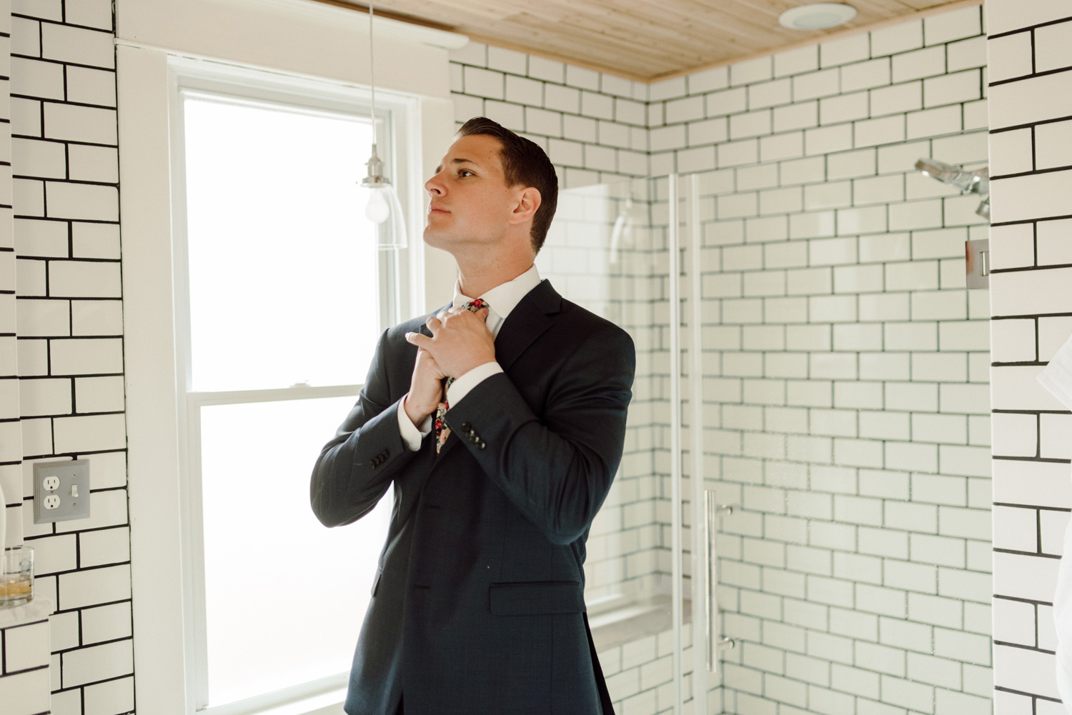 groom getting ready in subway tile bathroom