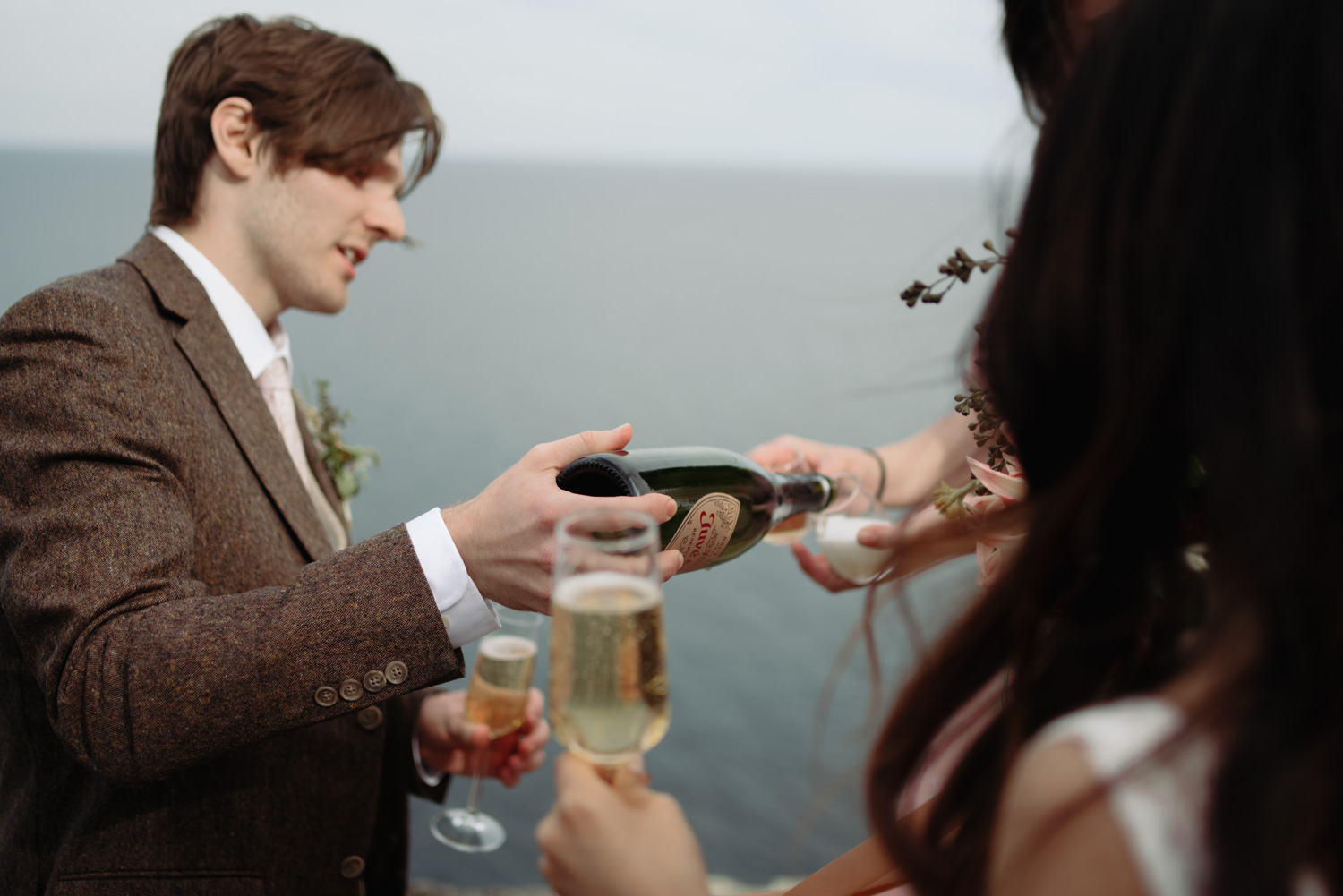 groom pouring champagne after wedding ceremony