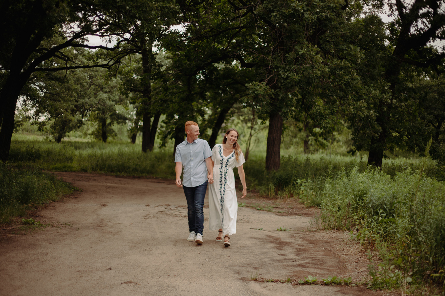 Engaged couple walking on dirt path