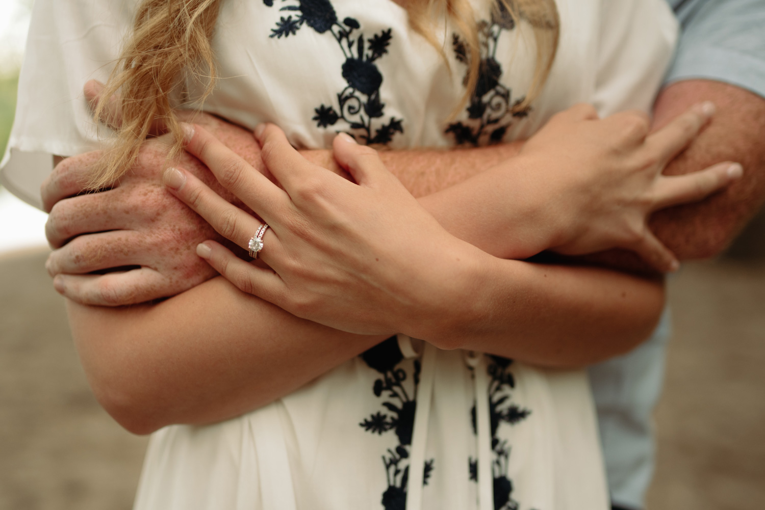 engaged couple embracing arms with engagement ring close up