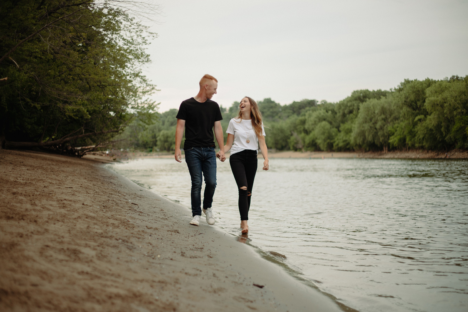 engaged couple walking along beach minnehaha river