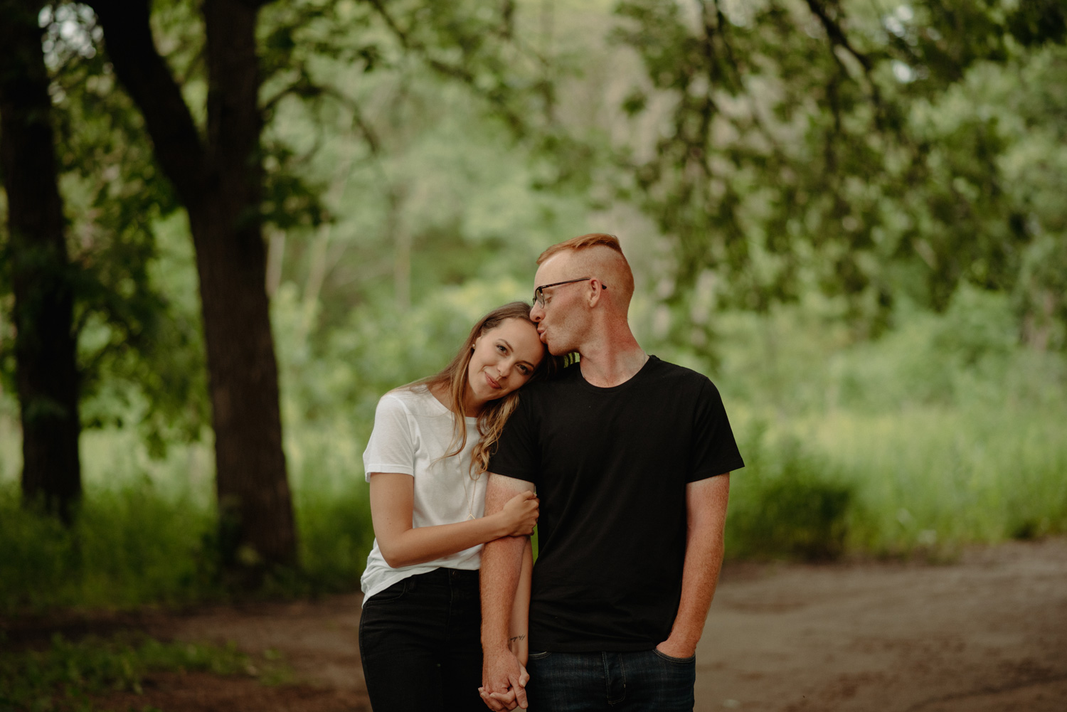 engaged couple walking on dirt path minnesota summer