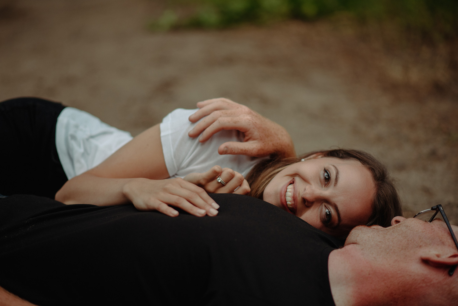 engaged couple laying down on dirt path minnesota park summer