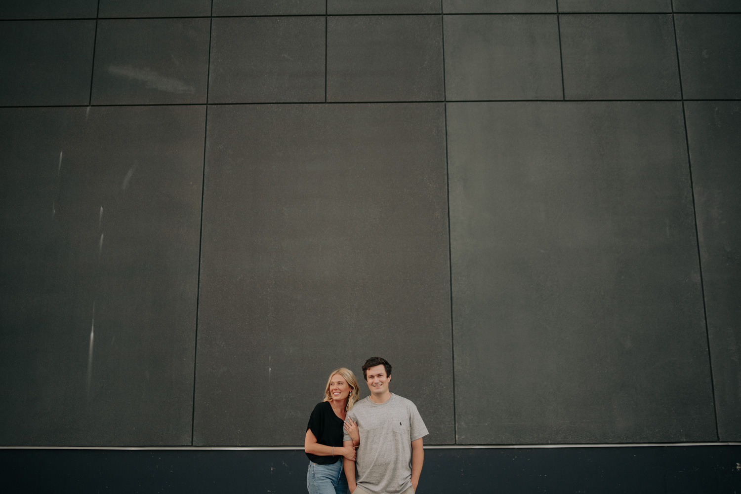 couple posing in front of grey wall north loop minneapolis