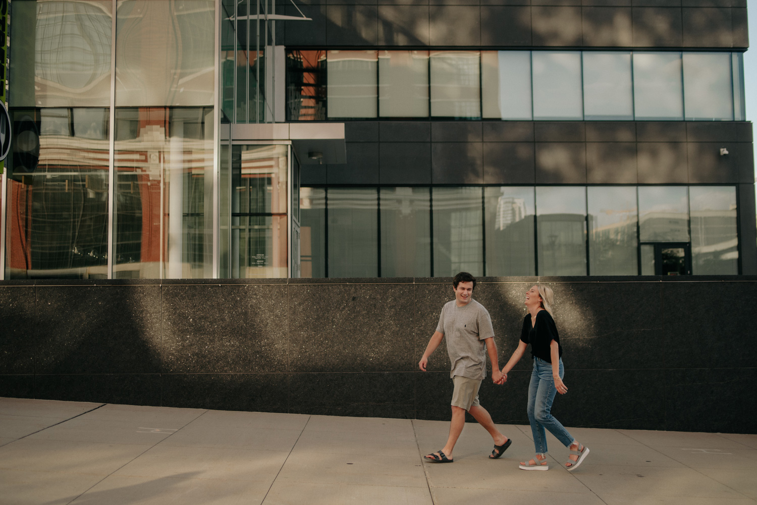 couple in front of glass warehouse building north loop minneapolis