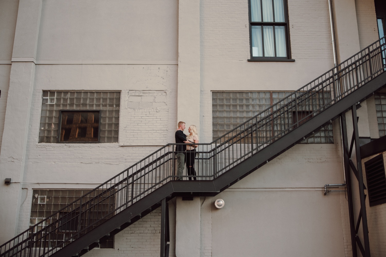 engaged couple on fire escape Minneapolis engagement photos