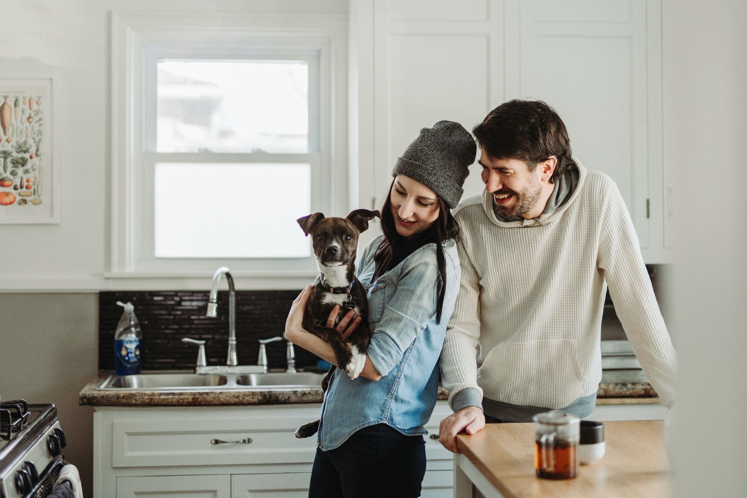 couple cuddling with dog in kitchen