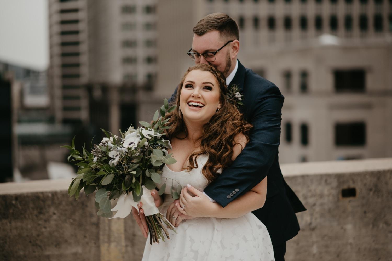 bride and groom laughing cuddling rooftop lumber exchange minneapolis