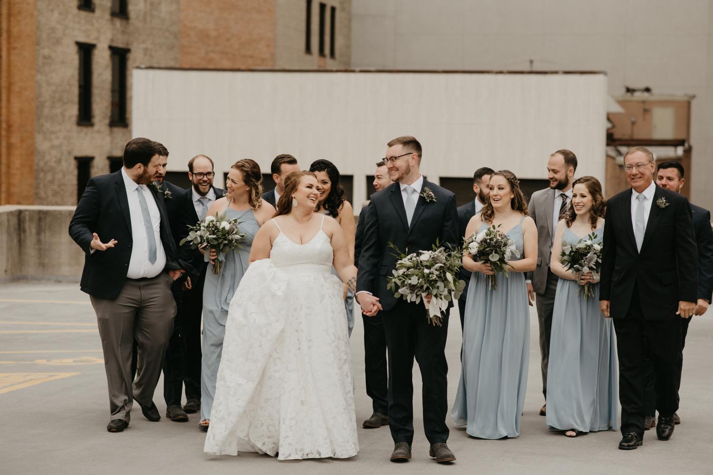 bride and groom walking with wedding party lumber exchange minneapolis