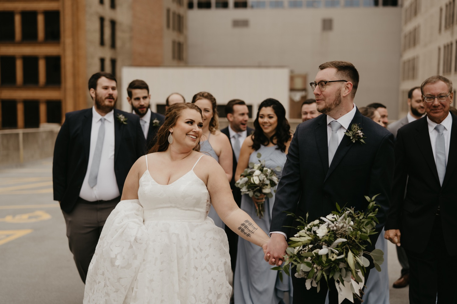 bride and groom walking on a rooftop with wedding party lumber exchange minneapolis