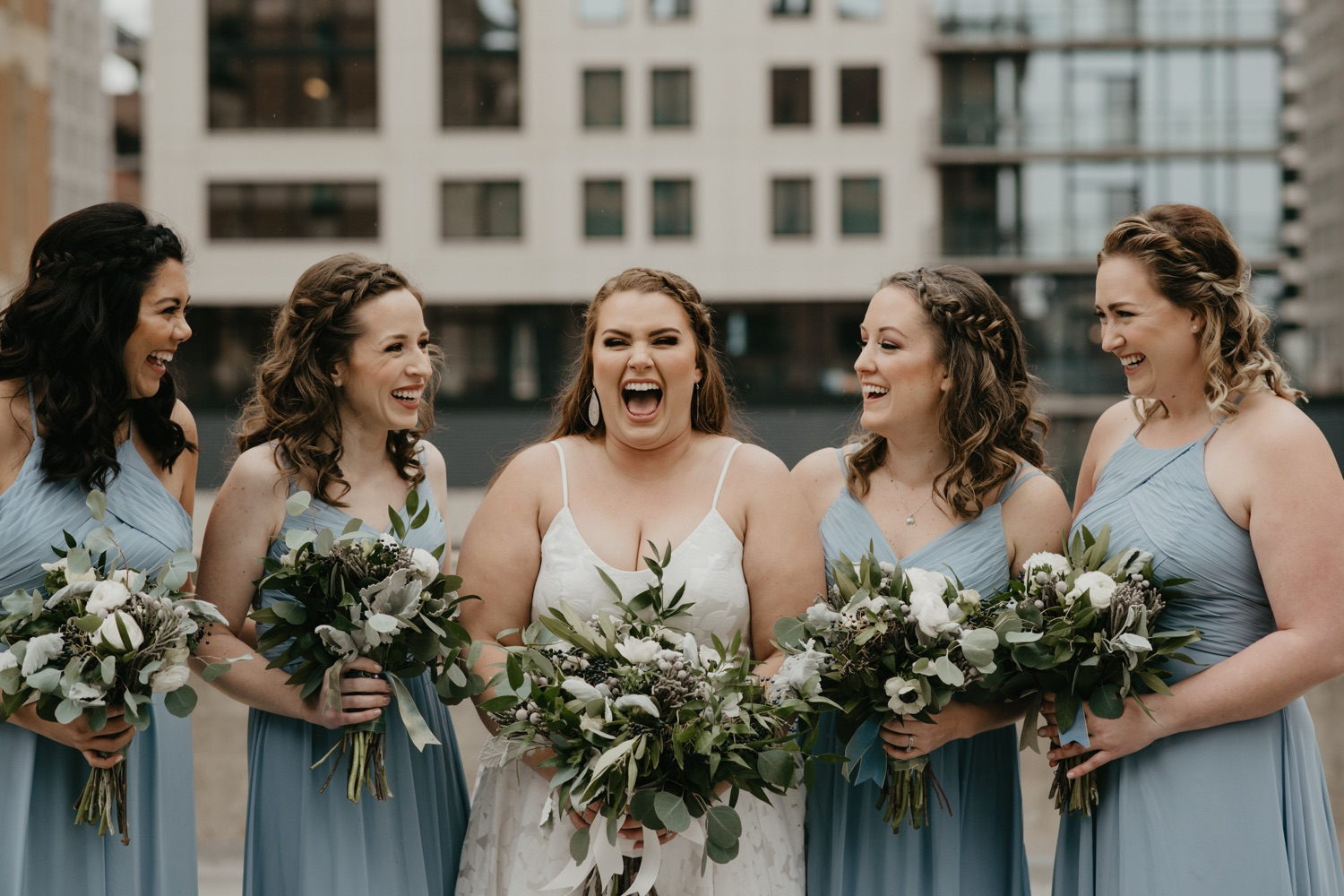 bridesmaids laughing on a rooftop lumber exchange minneapolis
