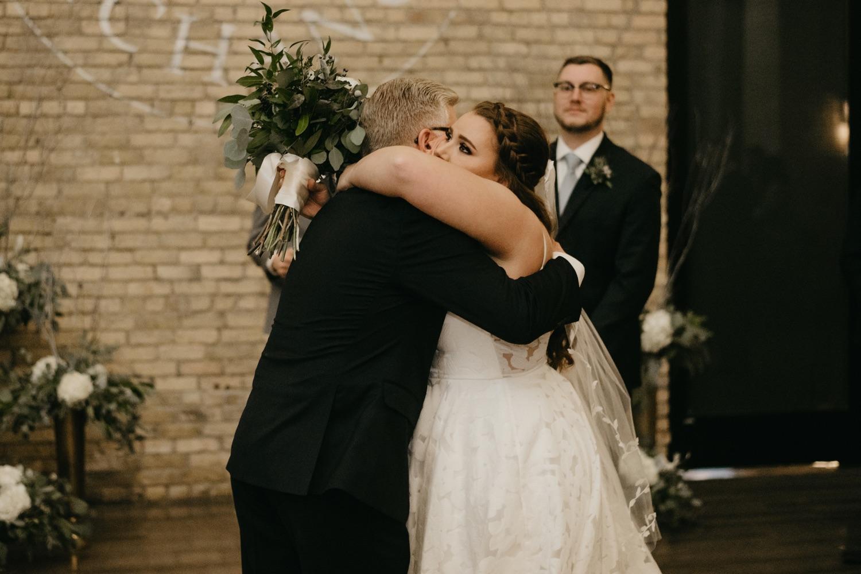 bride hugging dad wedding ceremony lumber exchange minneapolis