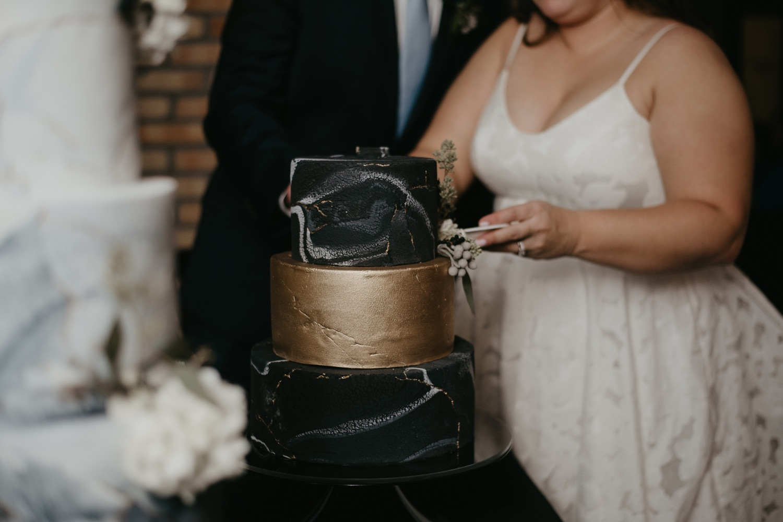 bride and groom cutting cake lumber exchange minneapolis wedding