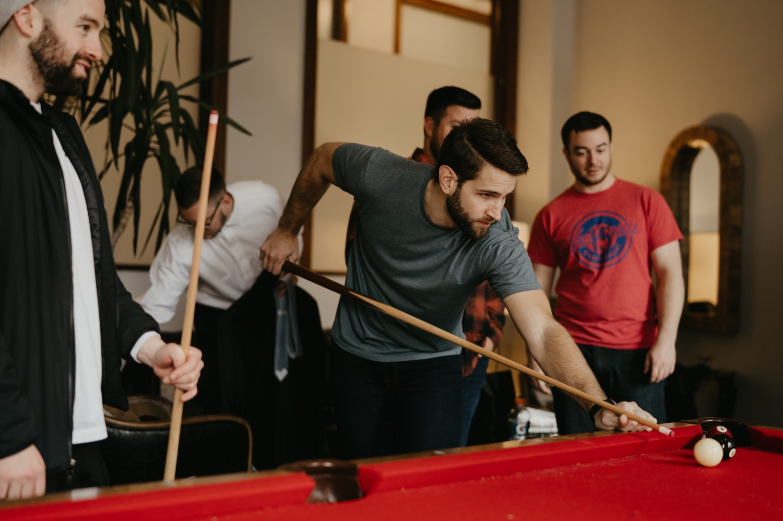 groomsmen playing pool wedding getting ready lumber exchange minneapolis