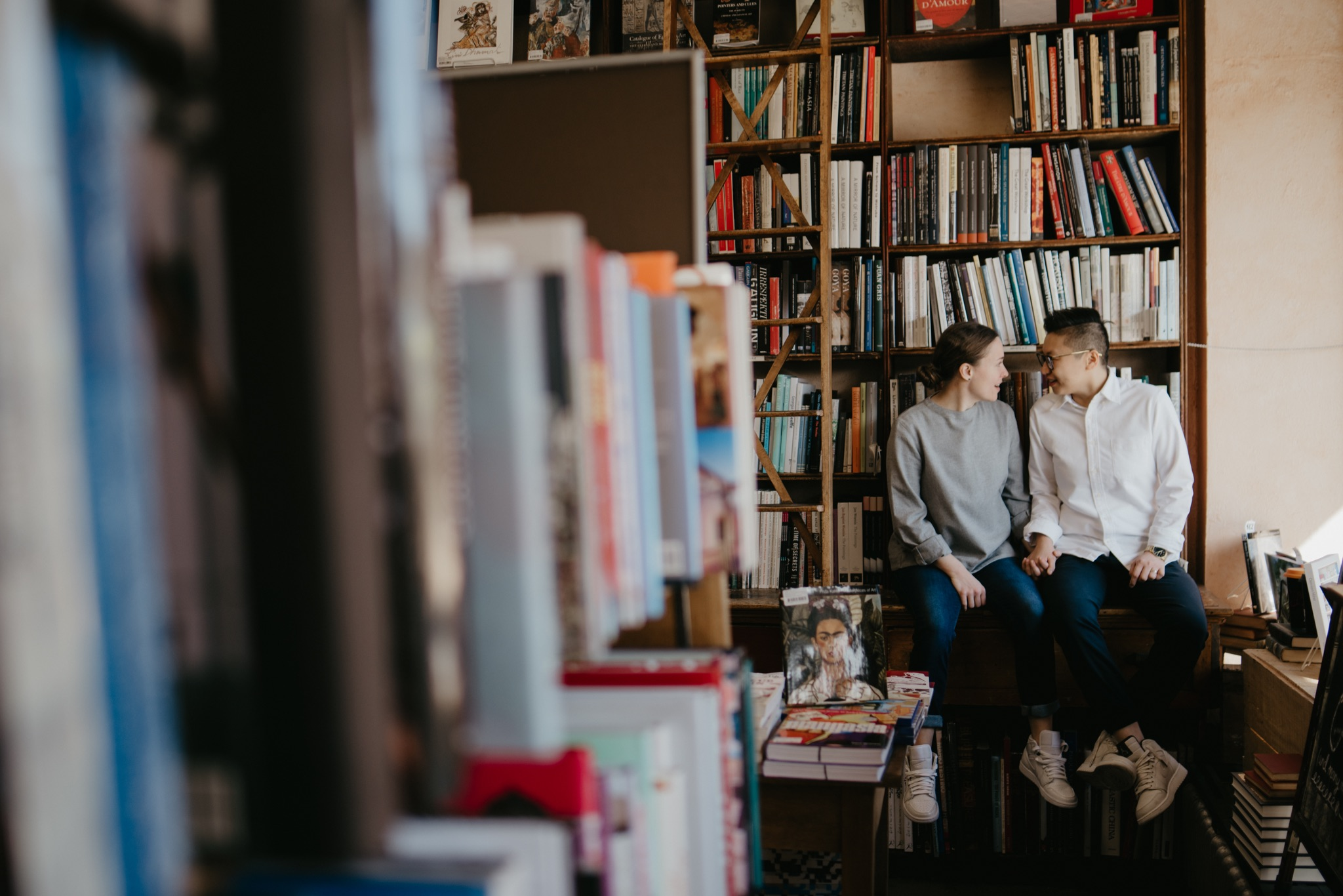 bride and bride sitting a bookstore looking at each other