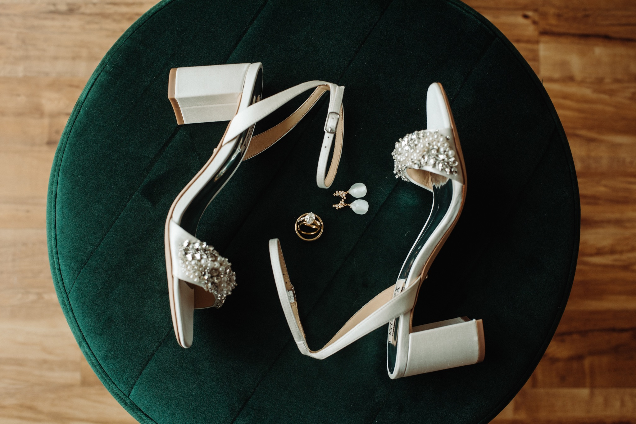 bride's white shoes, earring, wedding ring on green background