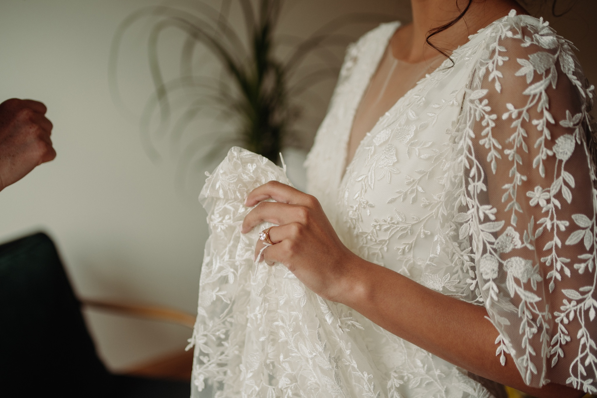 Bride holding up her dress in her hands to her chest