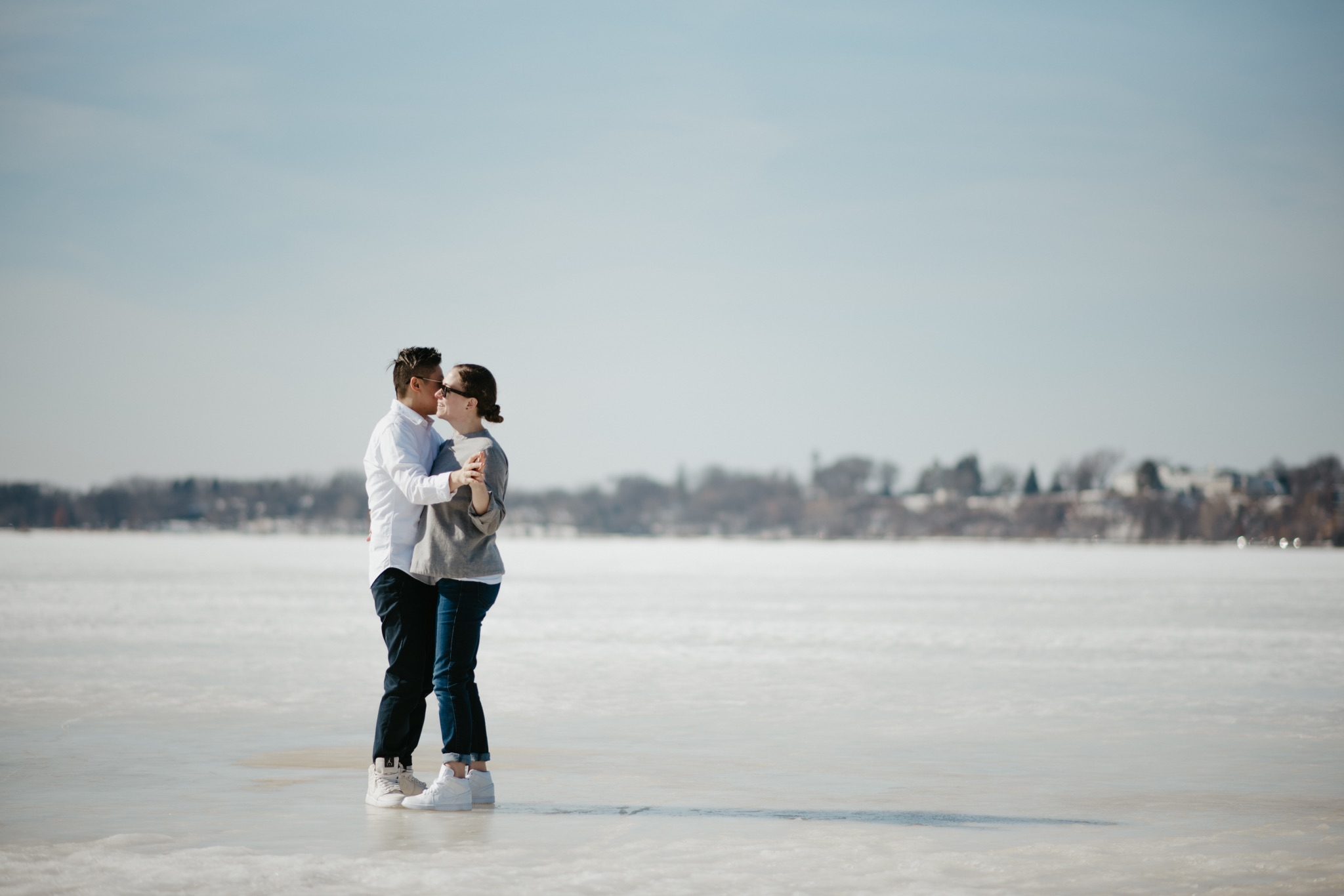 bride and bride standing on a frozen lake hugging and kissing
