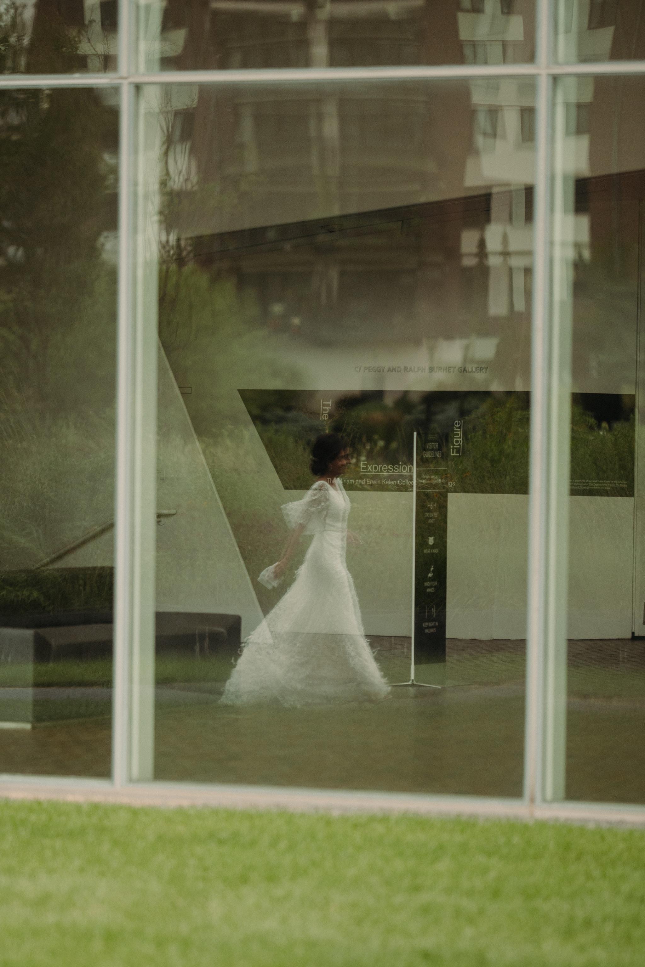 Reflection of the bride walking in a window walker art center wedding