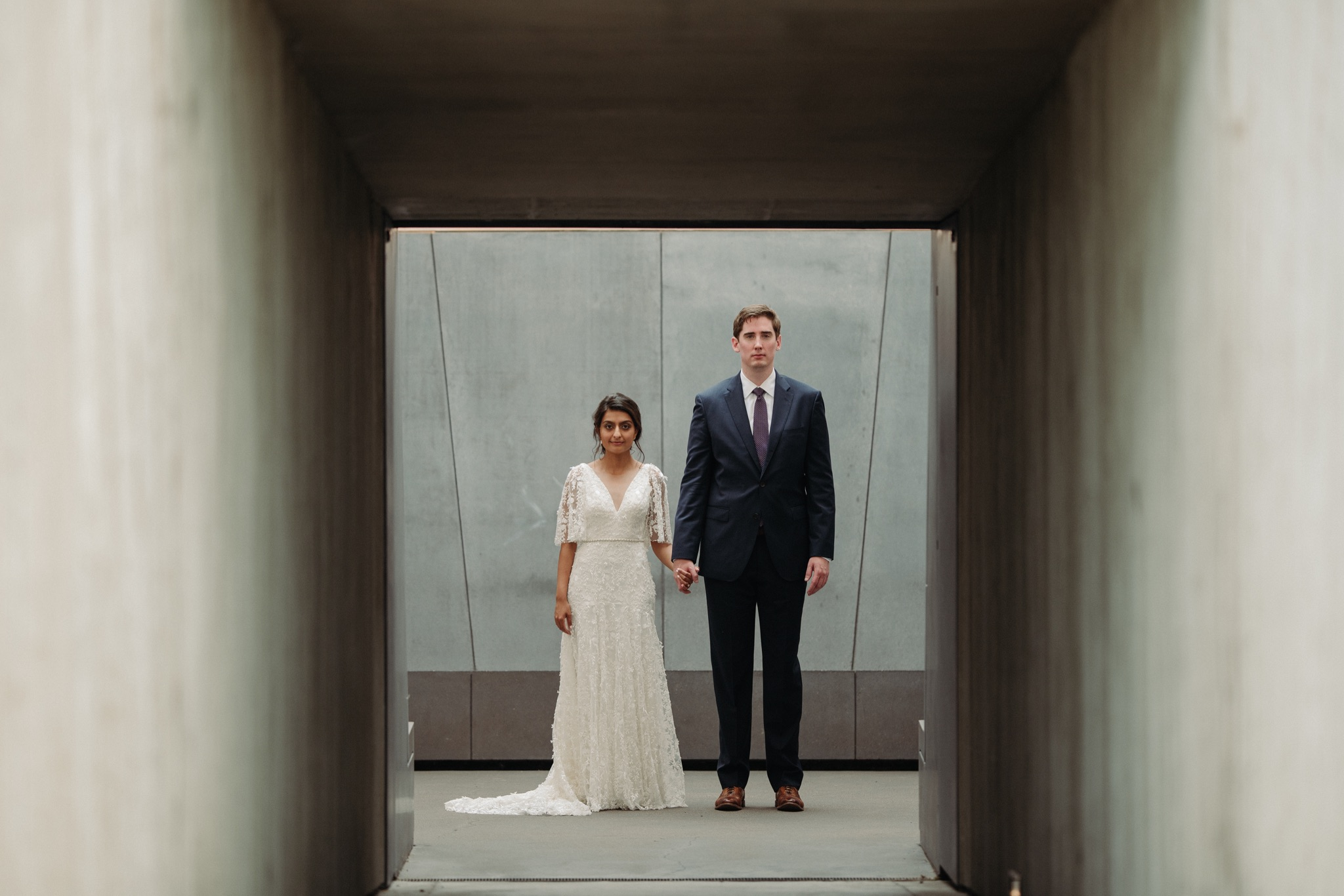 Bride and groom standing next to each other under a tunnel walker art center wedding