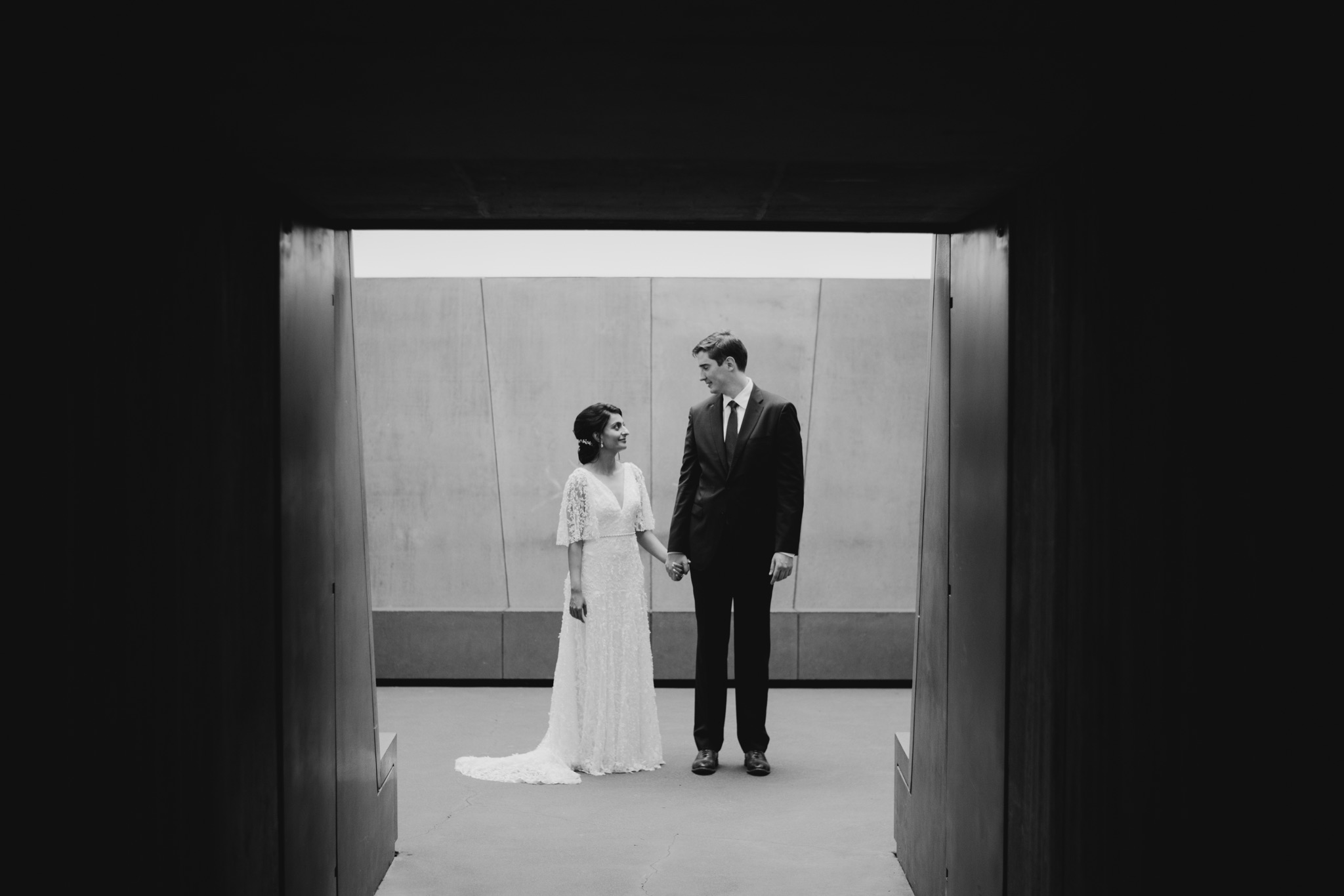 Bride and groom holding hands and looking at each other under a tunnel walker art center wedding
