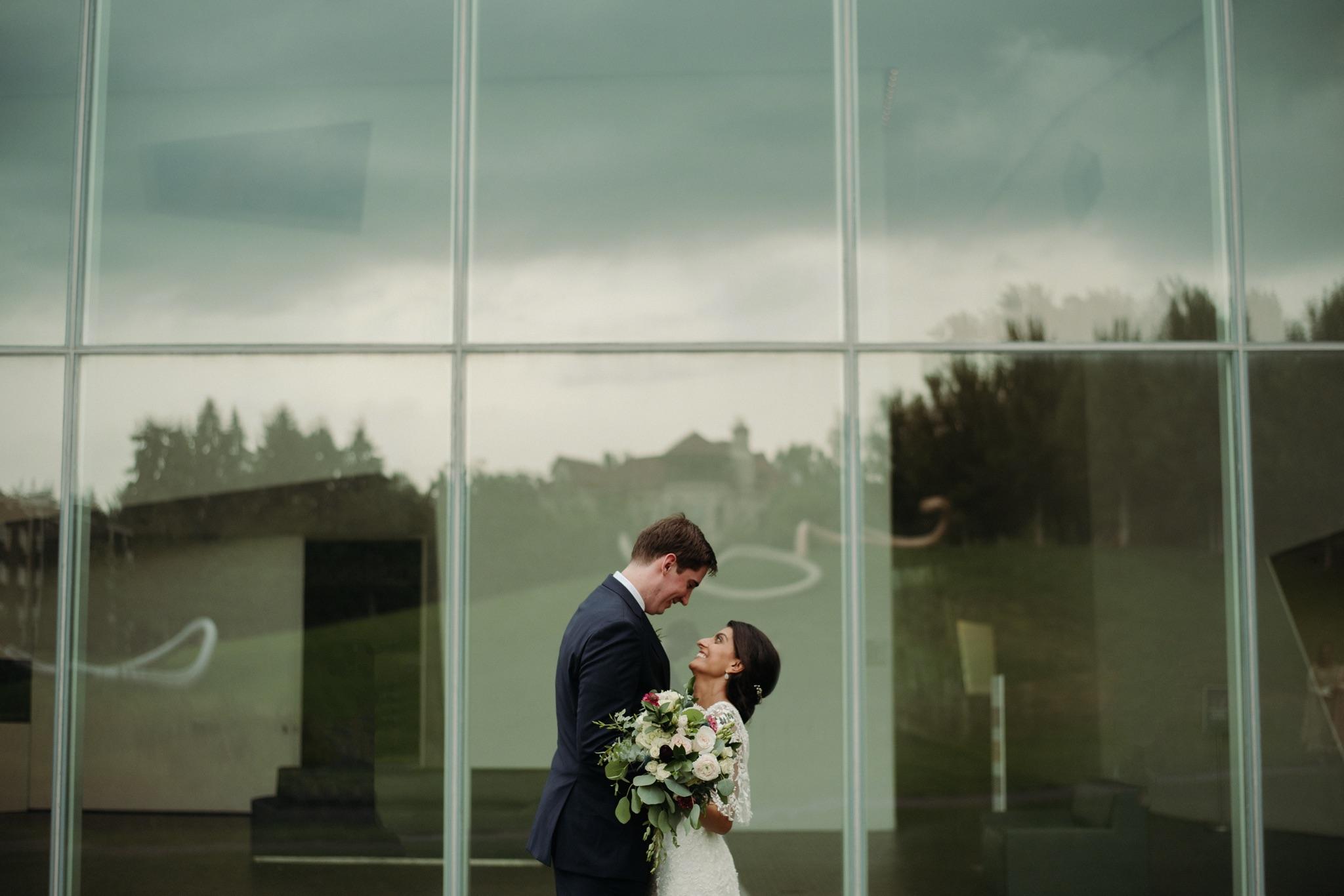 Bride and groom hugging in front of a window walker art center wedding