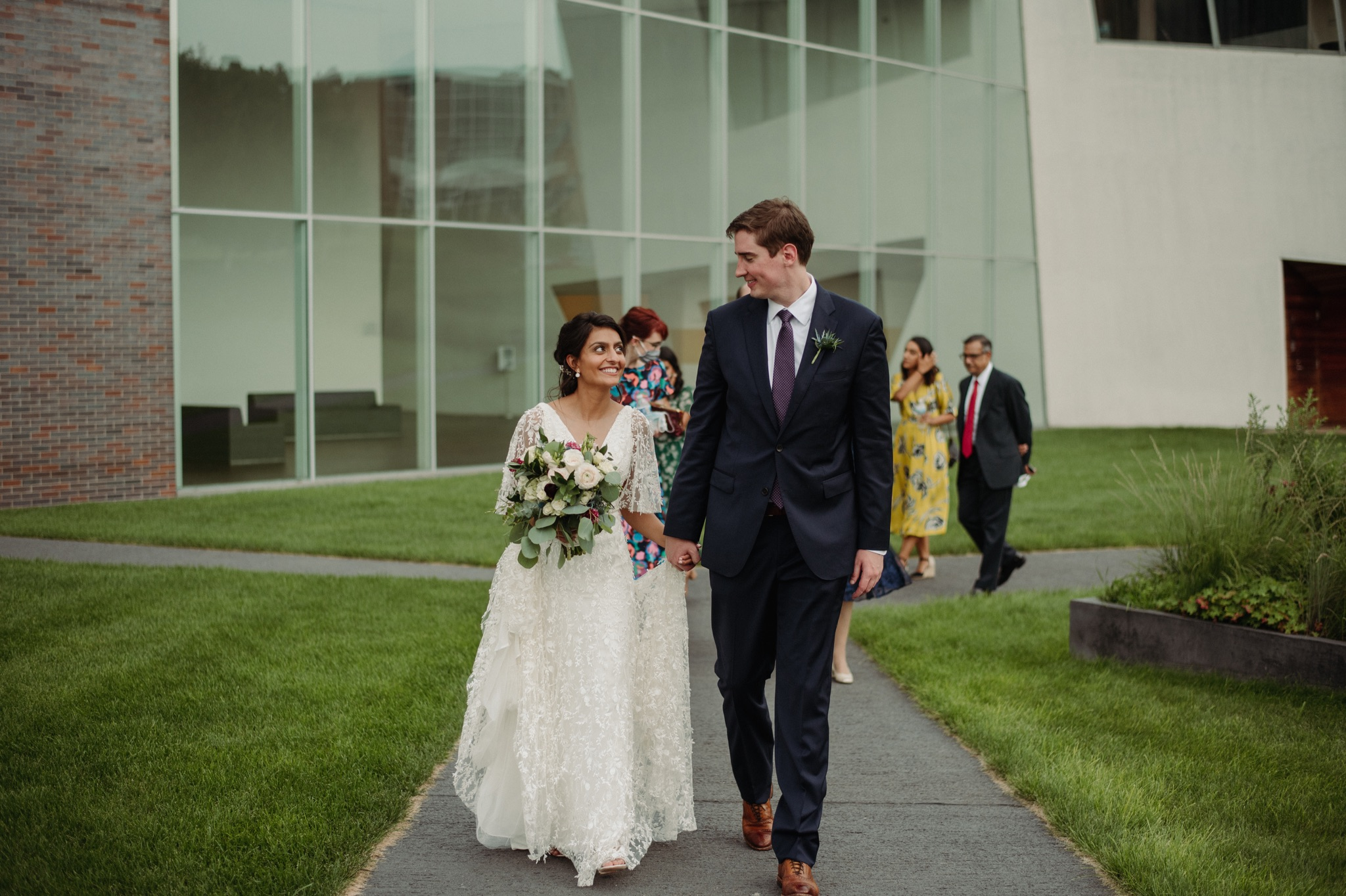 Bride and groom smiling at each other and walking next to each other while holding hands walker art center wedding