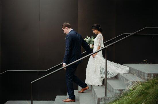 bride and groom walking down stairs, black background walker art center wedding