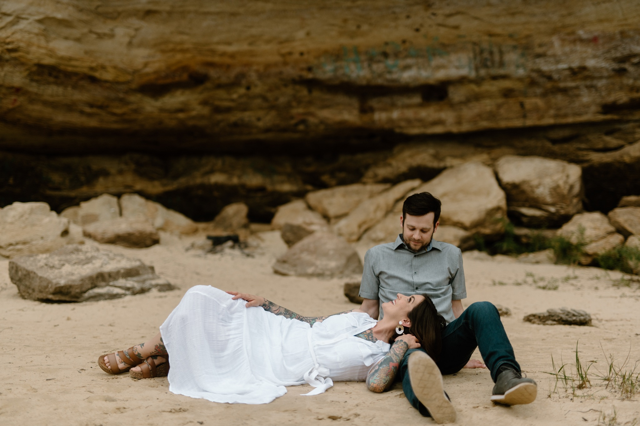 man sitting on beach and woman laying her head on man's lap