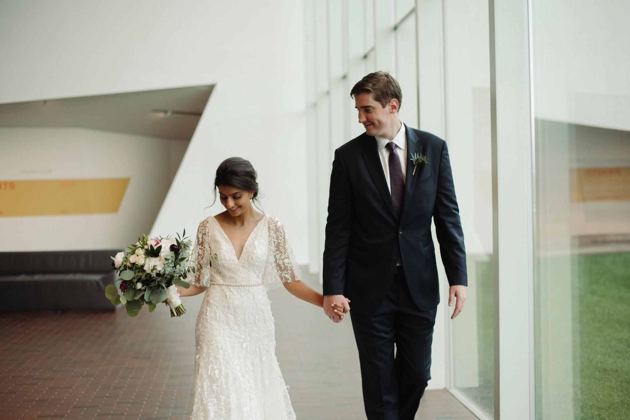 Bride and groom walking, bride has bouquet in her right hand walker art center wedding