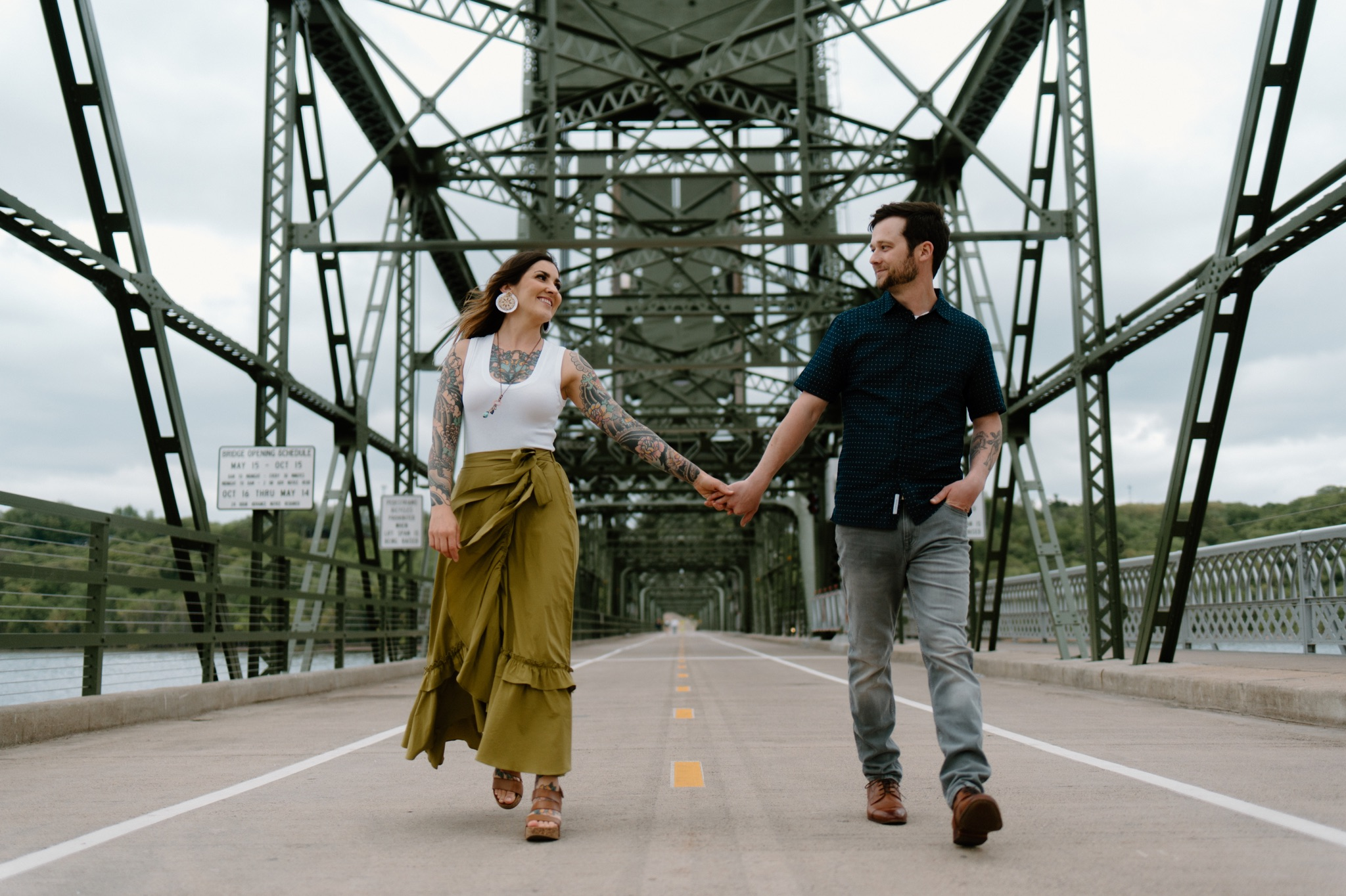 man and woman walking on a bridge and holding hands