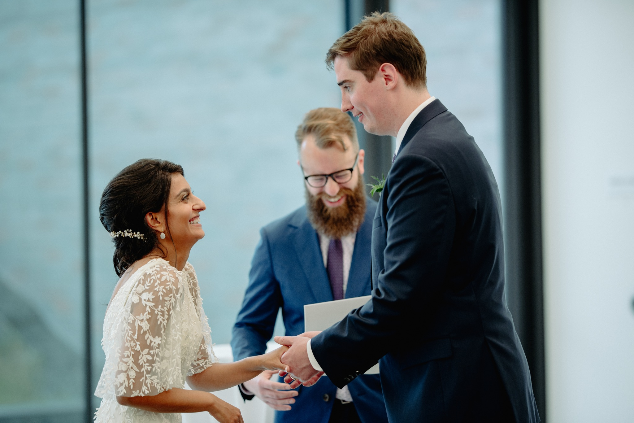 bride laughing and holding hands with groom facing each other walker art center wedding