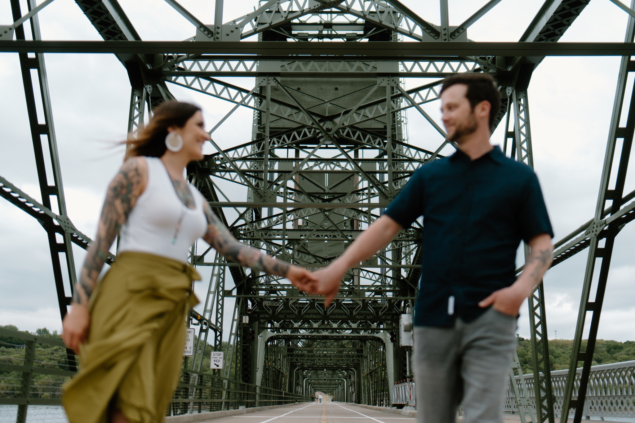 man and woman standing on a bridge holding hands