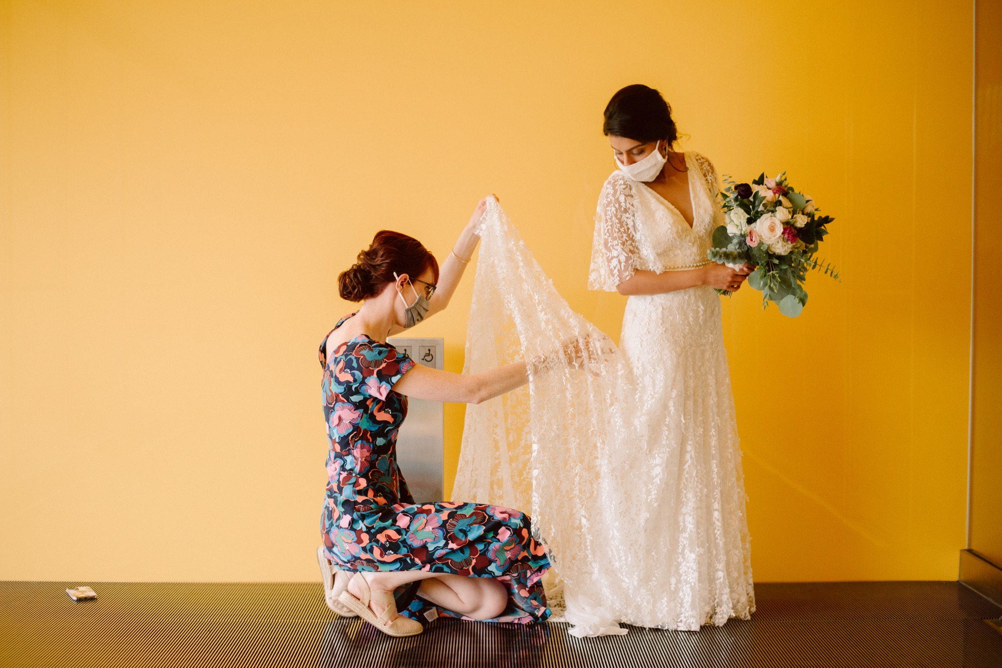 woman adjusting bride's wedding dress with a yellow wall in the background