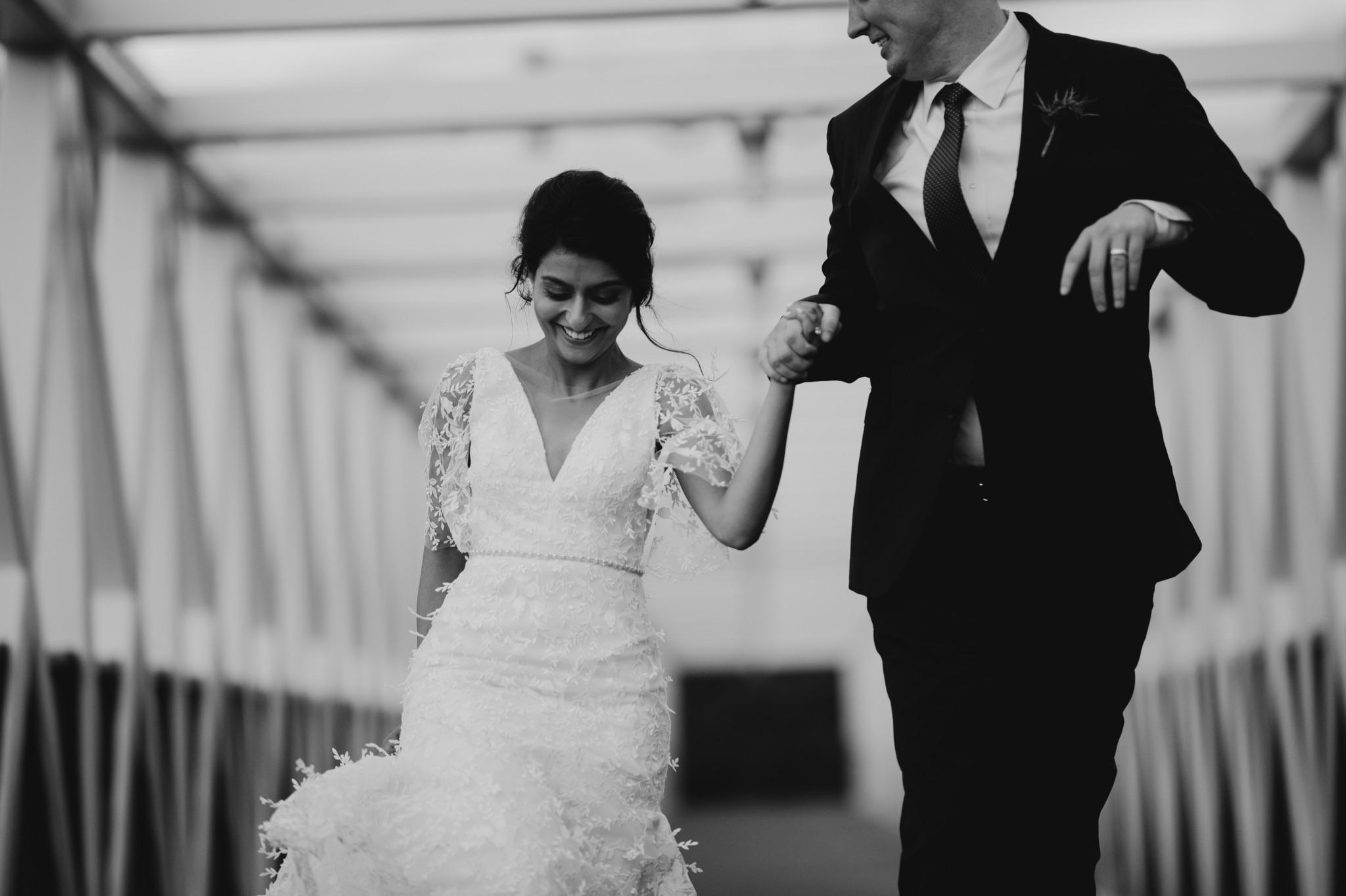 Bride and groom walking and groom looking at bride walker art center wedding