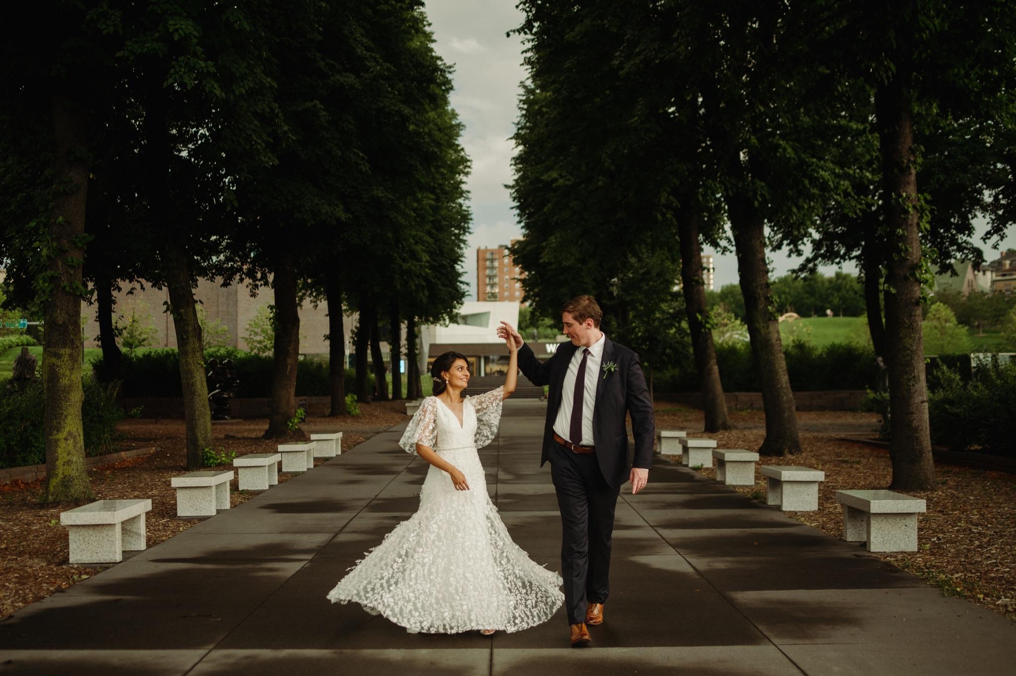 Groom spinning bride outside on sidewalk with trees in background walker art center wedding