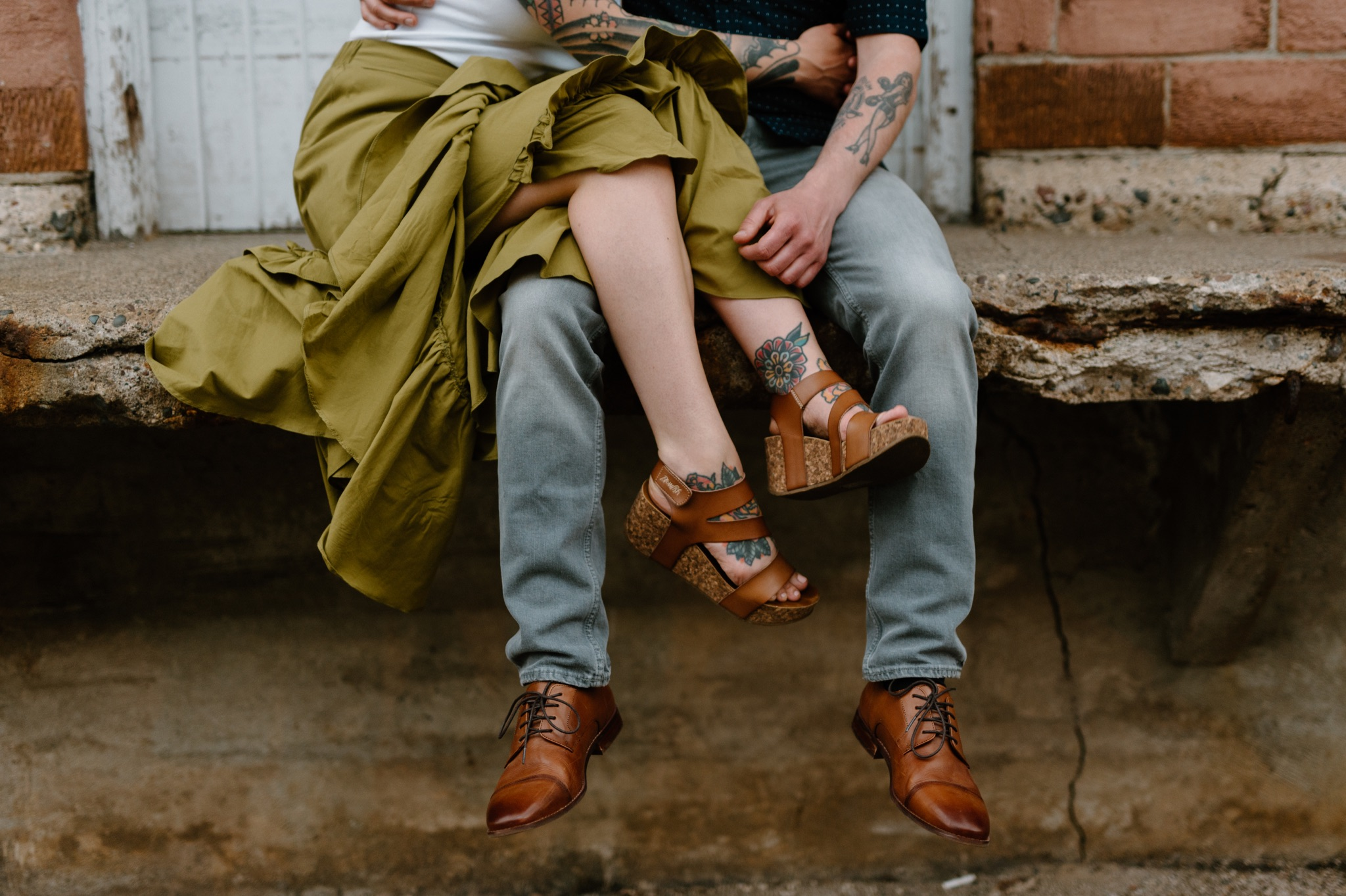 man and woman sitting down and woman has her legs crossed over man's legs