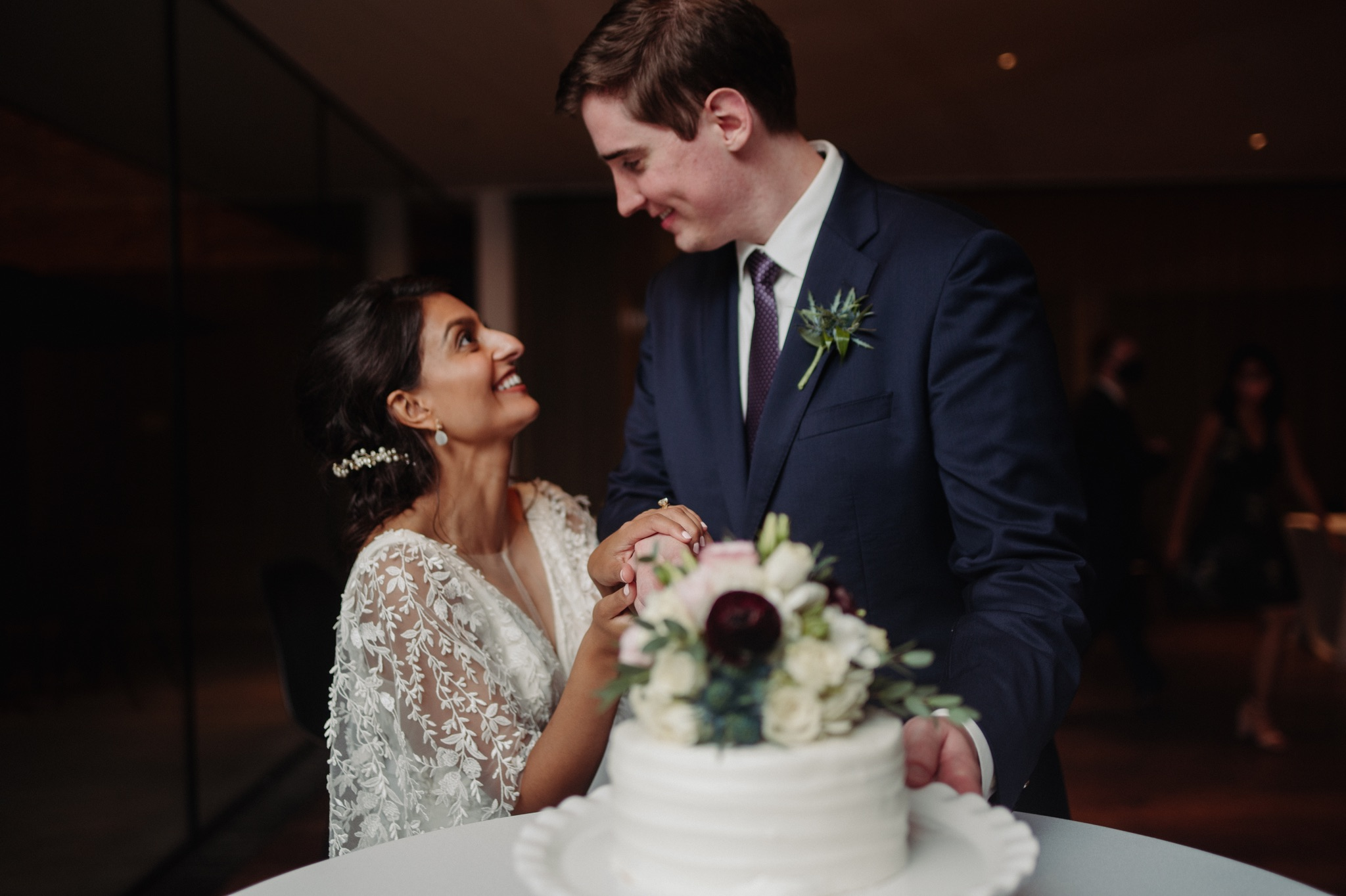 bride and groom standing behind a cake on a table looking at each other walker art center wedding
