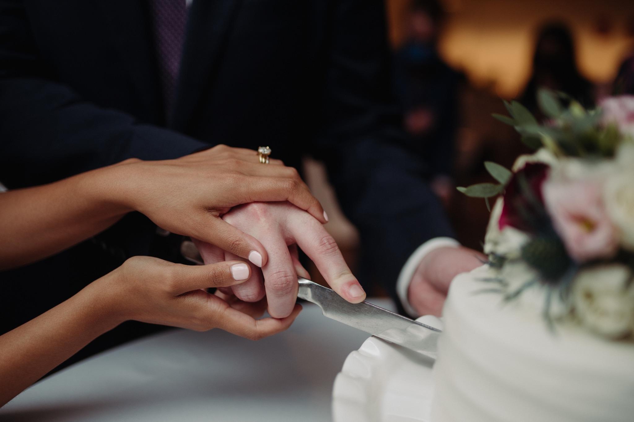 bride and groom's hands cutting a cake walker art center wedding