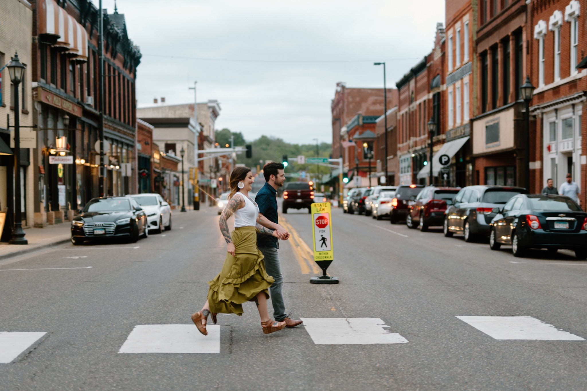 man and woman holding hands and walking across a street in a crosswalk
