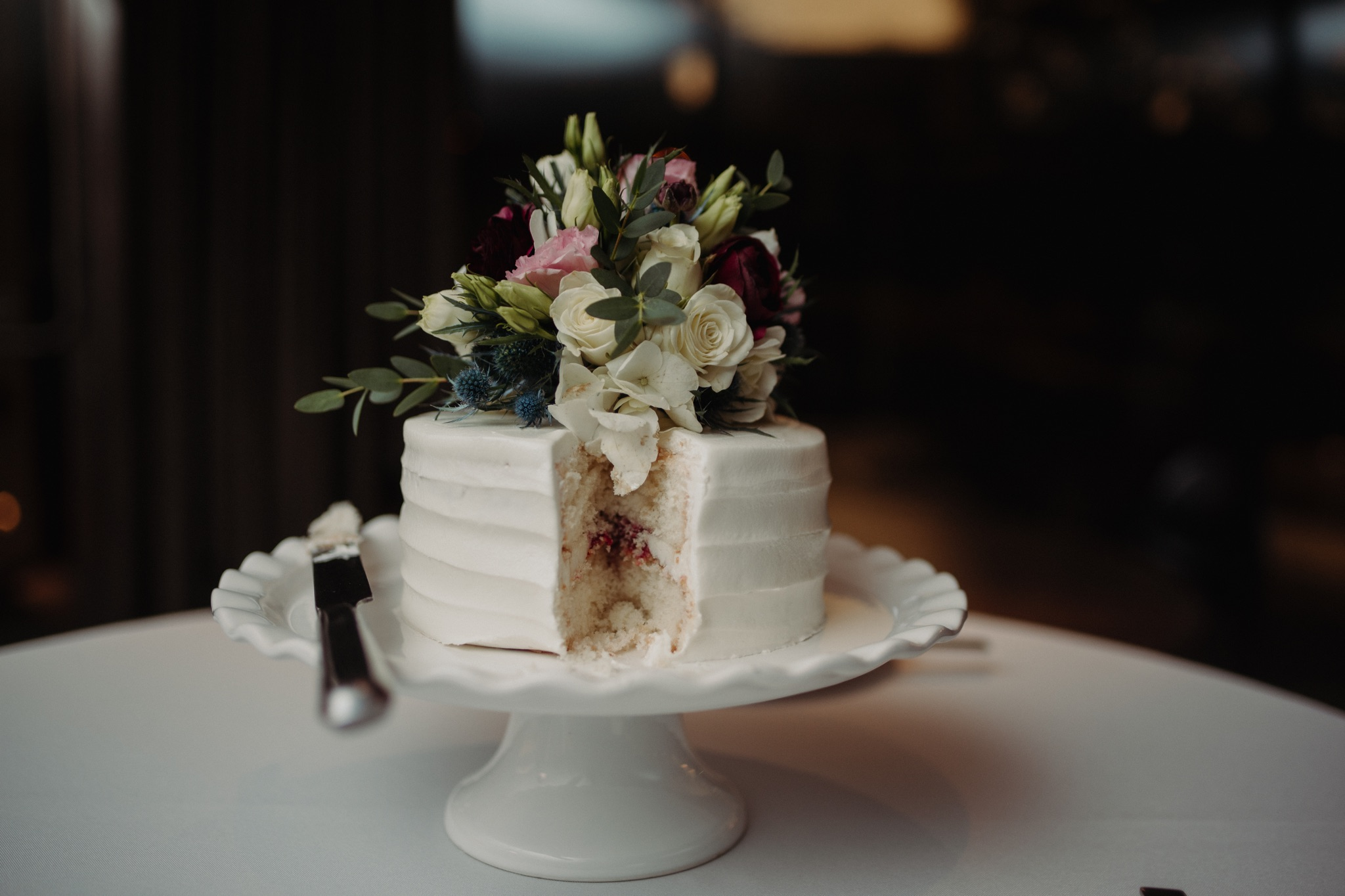 white cake with flowers on top on a raised cake plate walker art center wedding