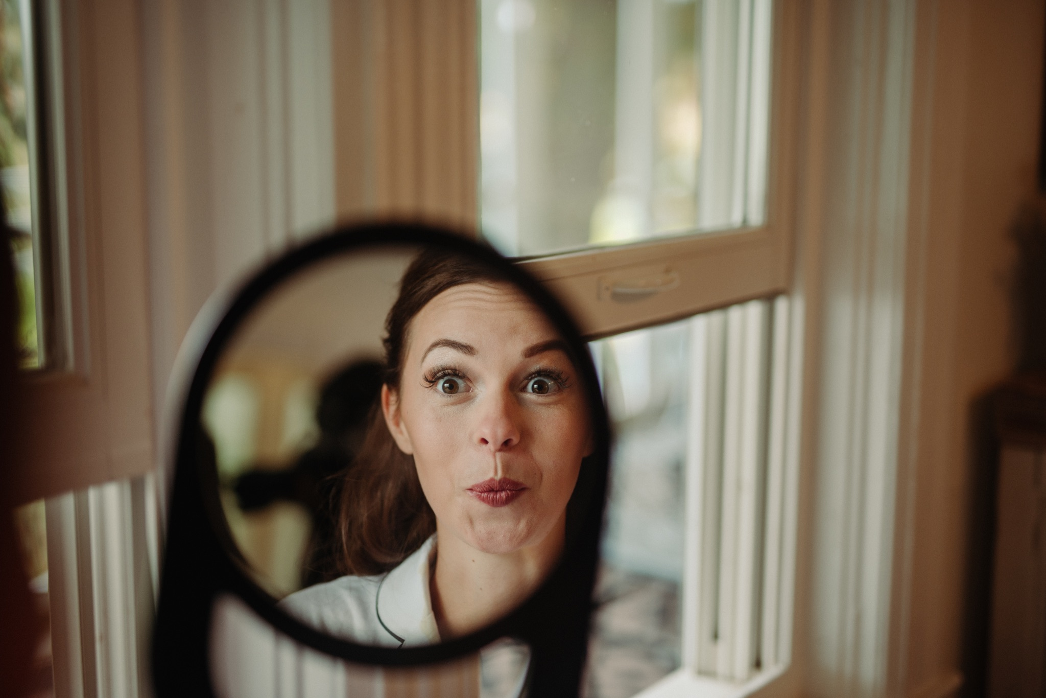 bride making a surprised face in a mirror