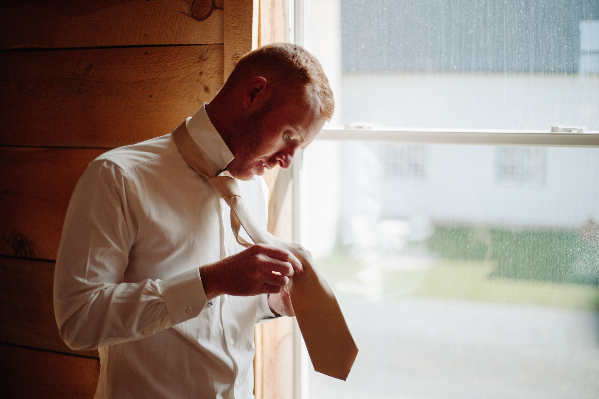 Groom holding his tie and getting ready