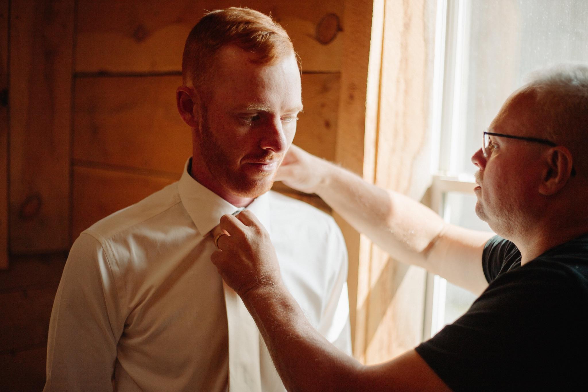 father of bride helping groom straighten tie