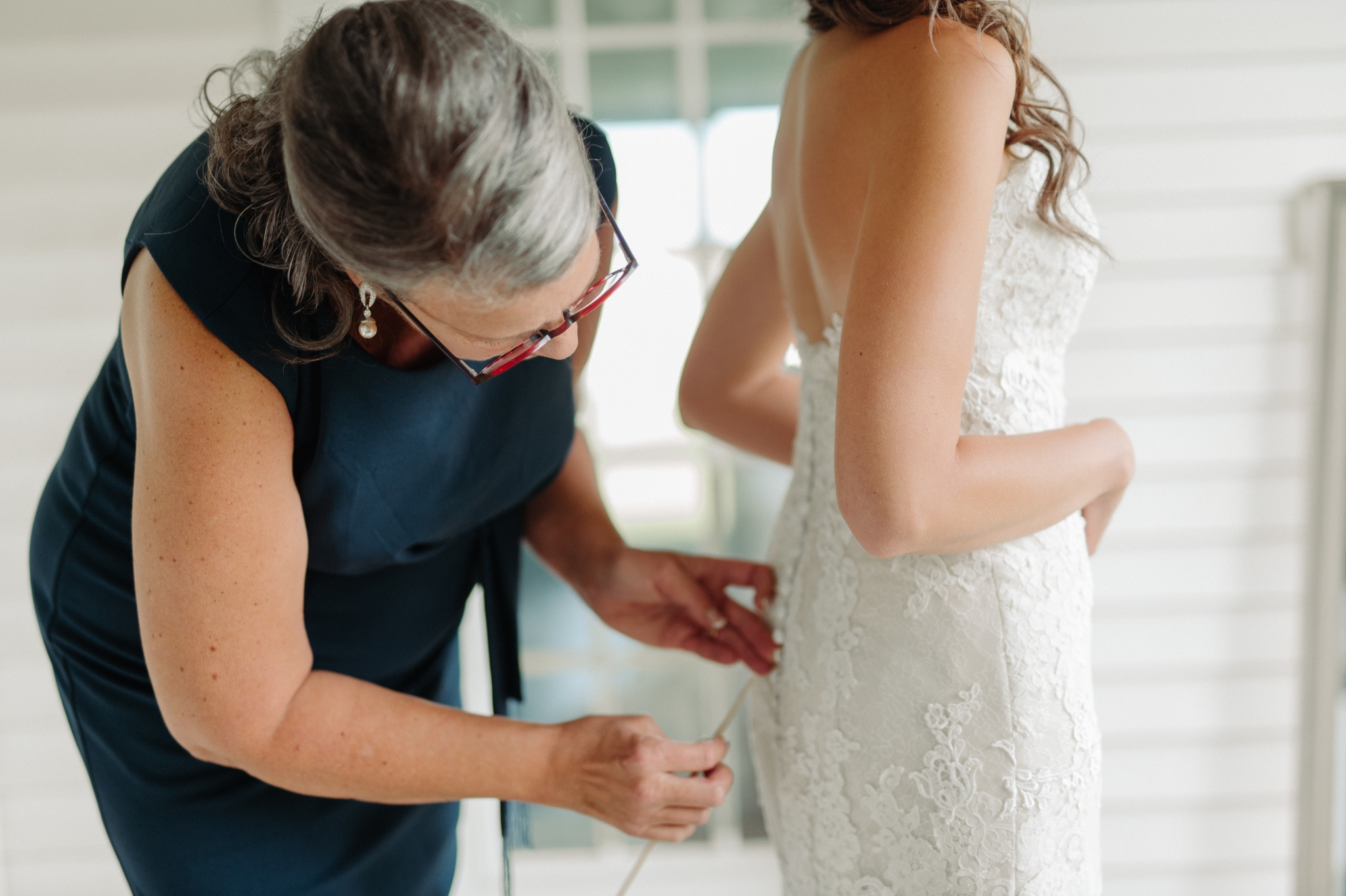 mother of bride helping bride with dress
